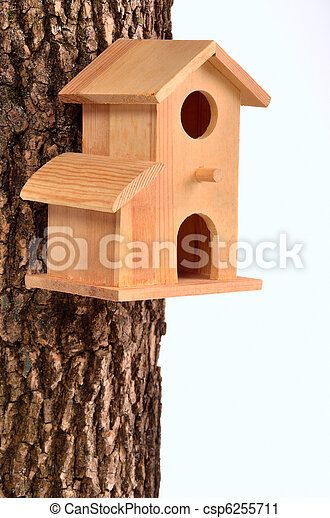 Comfortable starling-house on a tree trunk isolated - csp6255711