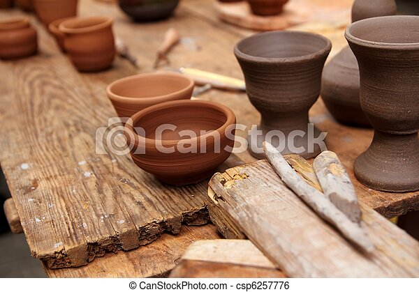 clay pottery potter handcrafts on vintage table - csp6257776