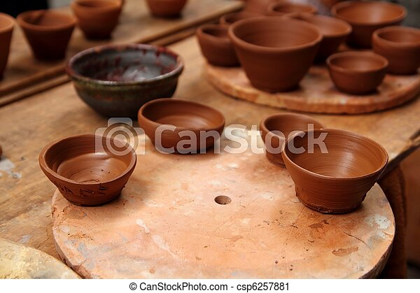 clay pottery potter handcrafts on vintage table - csp6257881