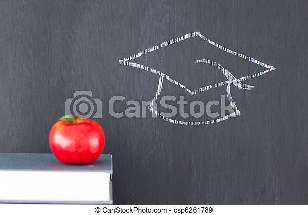 Stack of books with a red apple and a blackboard with a graduation cap drawn on it - csp6261789