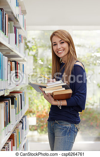 girl choosing book in library and smiling - csp6264761