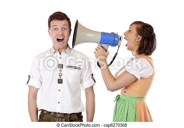 Frustrated woman with Dirndl screams into ear of husband with megaphone - csp6270368