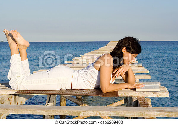 woman relaxing reading book on summer vacation - csp6289408