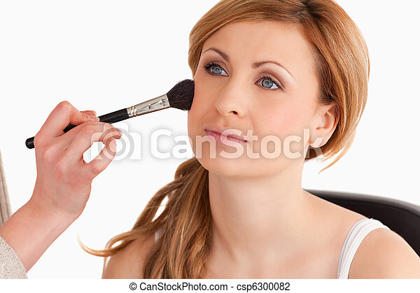 Blonde woman being made up by a make-up artist in a studio - csp6300082