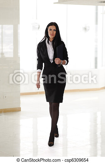 A pretty business woman walking indoor, modern business office
