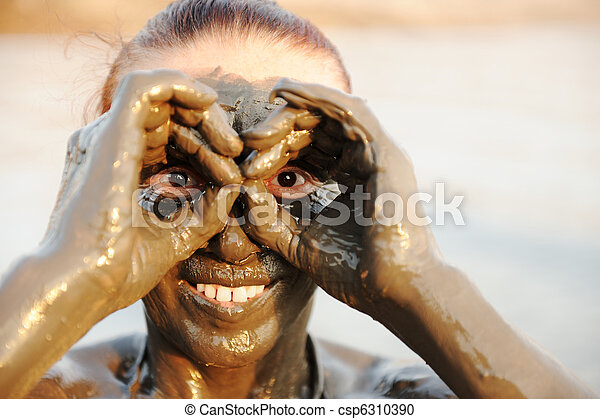An elderly woman enjoying the natural mineral mud on face sourced from the dead sea in background - csp6310390