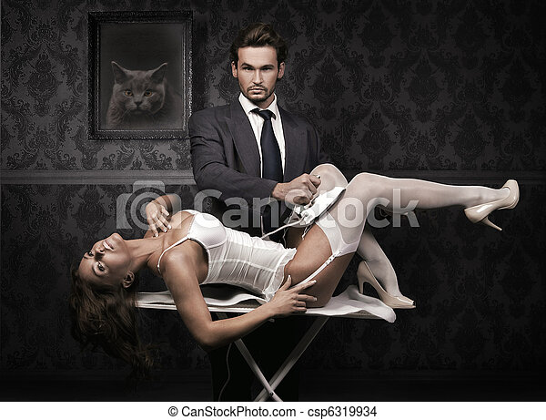 Handsome man ironing attractive brunette - csp6319934