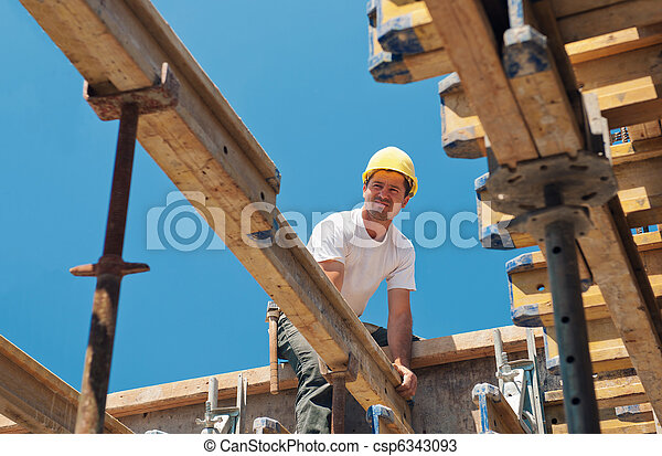 Construction worker placing formwork beams - csp6343093