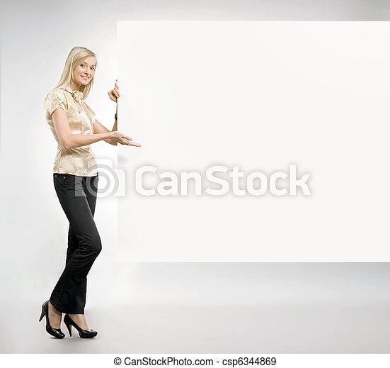 Pretty blonde secretary showing an empty board,lots of copyspace - csp6344869