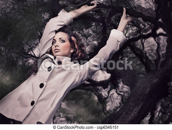 Fine ART style photo of a gorgeous brunette holding branch - csp6345151