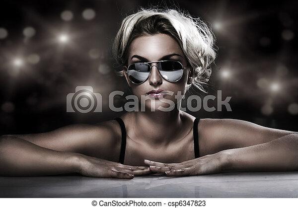 studio shot of young blonde wearing stylish sunglasses - csp6347823