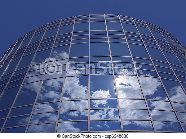 Windows of skyscraper with reflections against blue sky - csp6348030