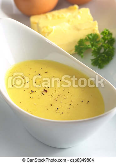 Hollandaise sauce with black pepper on top and its ingredients, egg and butter in the back (Selective Focus, Focus in the middle of the bowl) - csp6349804