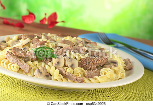 Veal strips with white mushrooms and onion in cream sauce served on fusilli pasta and garnished with a parsley leaf (Selective Focus, Focus on the parsley leaf and its surroundings) - csp6349925