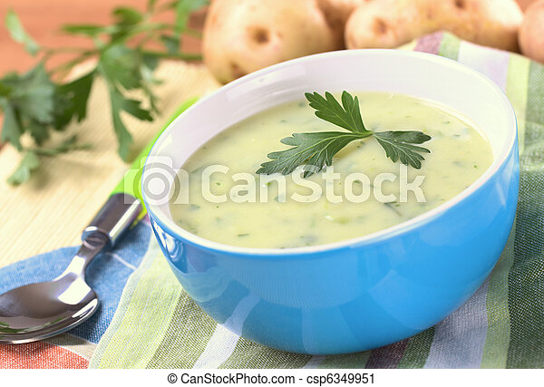 Cream of potato with herbs and green onions garnished with parsley and served in a blue bowl with potatoes and parsley in the back (Selective Focus, Focus on the front of the parsley) - csp6349951