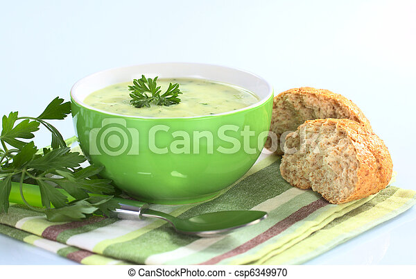 Cream of potato with herbs and green onions garnished with parsley and served in a green bowl with parsley and buns on the side photographed on bluish background (Selective Focus, Focus on the front o - csp6349970