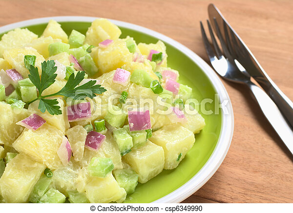 Potato salad with green and red onions and cucumber with a mayonnaise-cream dressing garnished with a parsley leaf (Selective Focus, Focus on the front of the salad)   - csp6349990