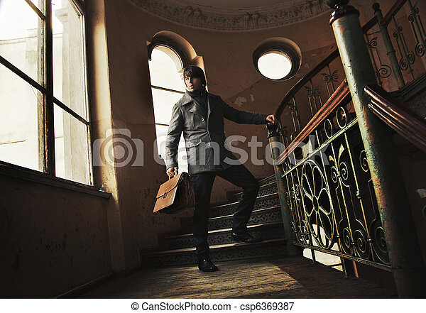 Man with a briefcase in a vintage interior - csp6369387