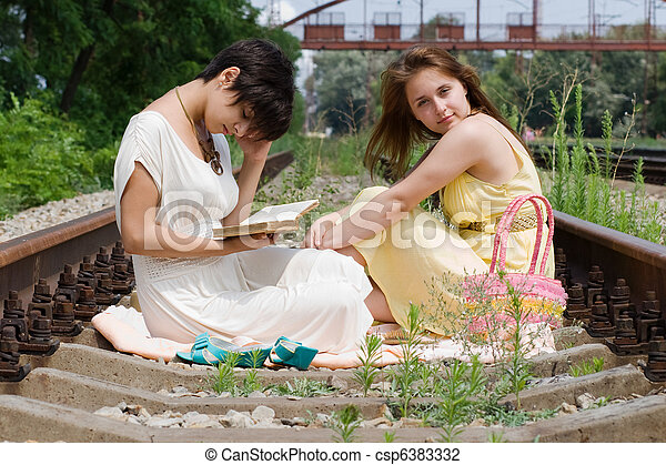 Girls sitting on the railroad carelessly - csp6383332