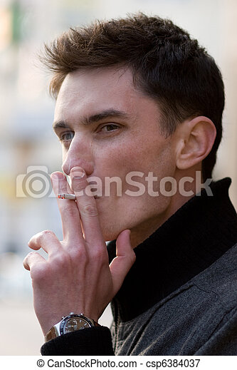Smoking young adult man - csp6384037