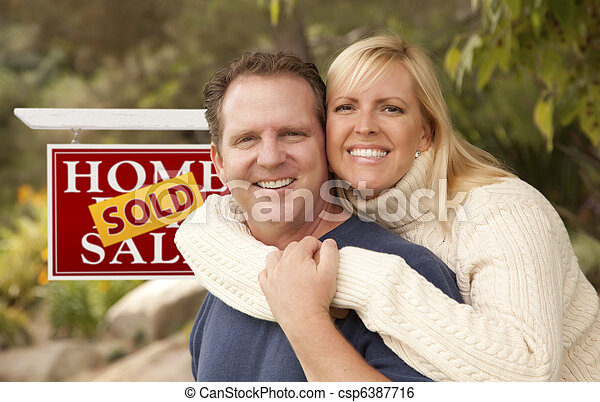 Happy Couple in Front of Sold Real Estate Sign - csp6387716