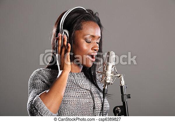Making music beautiful black woman singing in mic - csp6389827