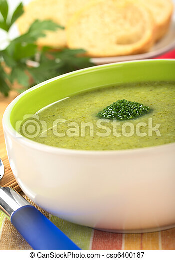 Cream of broccoli garnished with a broccoli floret on top with baguette slices and parsley leaves in the back (Selective Focus, Focus on the broccoli floret on the soup) - csp6400187