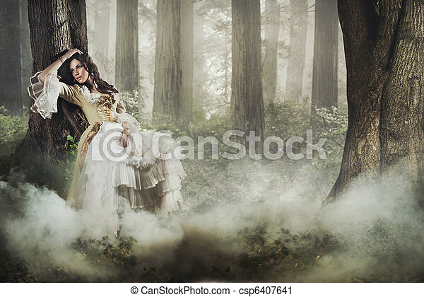 Fine art photo of a gorgeous lady in a mysterious foggy forest - csp6407641