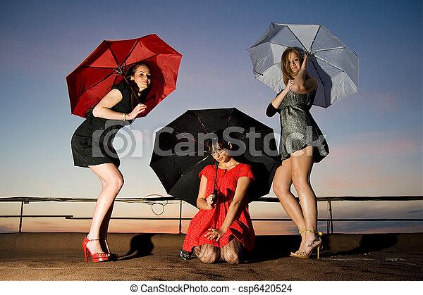 Three sexy chicks with umbrellas posing on the roof - csp6420524