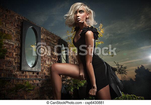 Beautiful blonde posing over evening sky - csp6430881