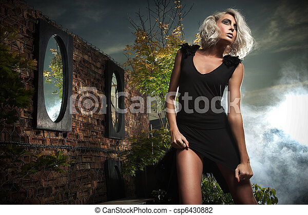 Beautiful blonde posing over evening sky - csp6430882