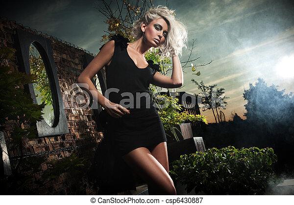 Beautiful blonde posing over evening sky - csp6430887