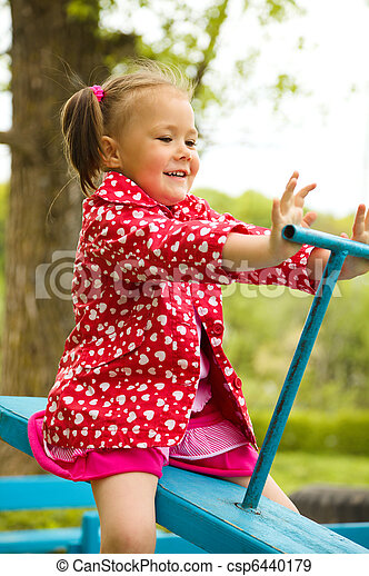 Cute little girl is swinging on see-saw - csp6440179