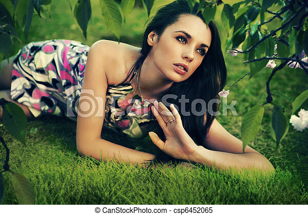 Young beauty brunette laying on the grass - csp6452065