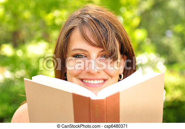 A young woman reading a book outdoors
