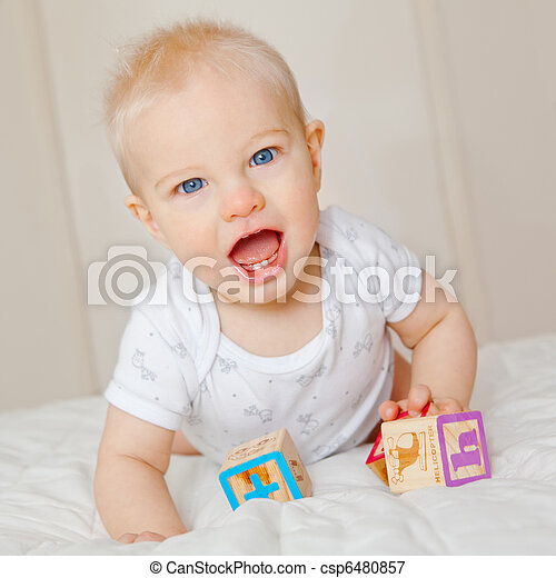 A 7 month old baby boy looking up from playing with blocks - csp6480857