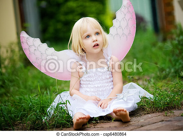 A innocent looking little girl dressed in a angel costume - csp6480864