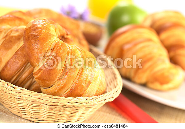 Fresh croissants in bread basket with a red knife beside, and a plate with croissants, green apple and orange juice in the back (Selective Focus, Focus on the front of the croissant in the basket) - csp6481484