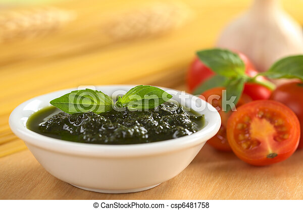 Fresh pesto made of basil, garlic and olive oil in a small bowl and garnished with a basil leaf with raw spaghetti, cherry tomatoes, basil leaves and garlic in the back (Selective Focus, Focus on the - csp6481758