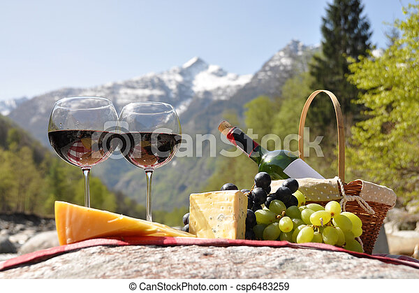 Red wine, cheese and grapes served at a picnic. Verzasca valley, Switzerland - csp6483259
