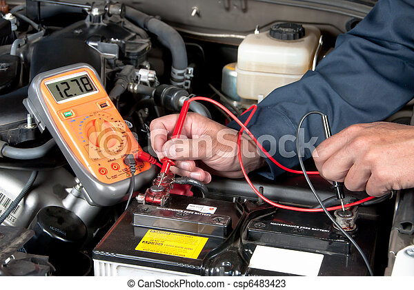 Auto mechanic checking car battery voltage - csp6483423