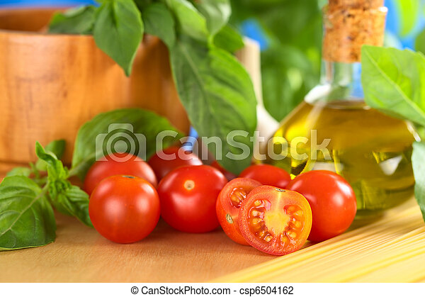Cherry tomatoes on wooden board with other ingredients such as olive oil, spaghetti and basil with a wooden mortar in the back (Selective Focus, Focus on the first tomato half) - csp6504162