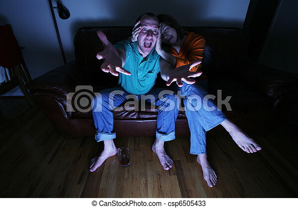 Husband and wife watching TV at home - csp6505433