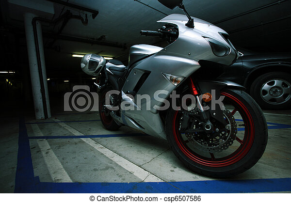 Metallic sport motorcycle parked in garage structure - csp6507586