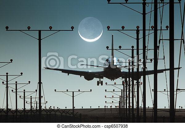 Plane landing in airport at night - csp6507938