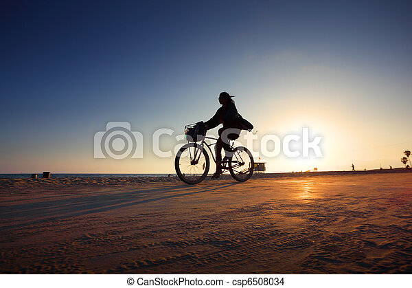 Biker silhouette riding along beach at sunset - csp6508034