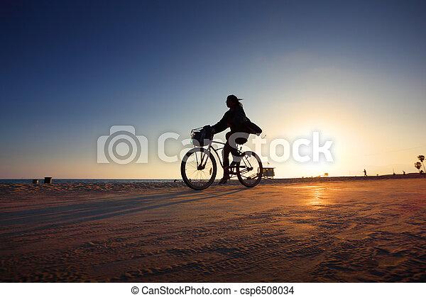 Biker silhouette riding along beach at sunset - csp6508034