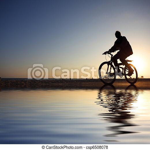 Biker silhouette riding along beach at sunset - csp6508078