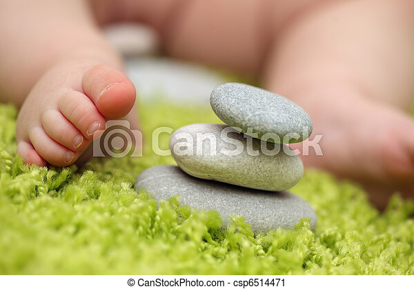 Baby feet next to stack of zen stones - csp6514471