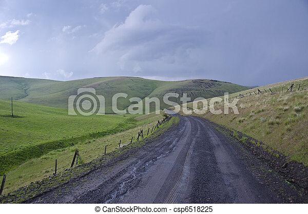 Gravel rural road beneath stormy sky - csp6518225